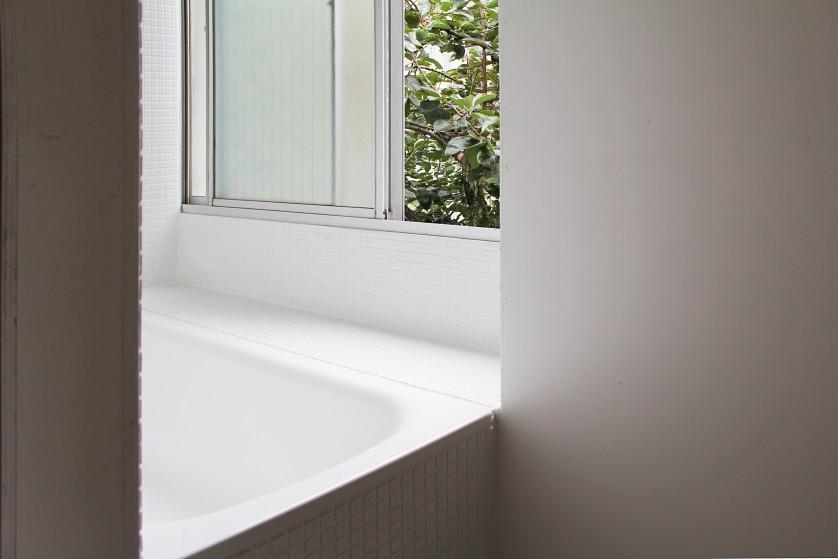 ©Yasuaki Morinaka 既存の出窓を活かしたバスタブの腰掛け。柿の木が見える