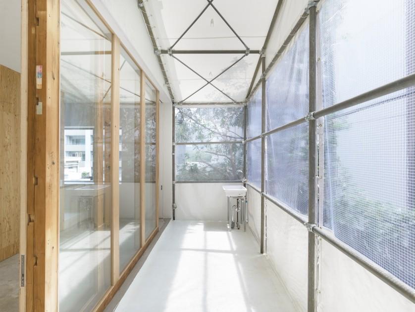 ©Sadao Hotta 既存のバルコニーにテントを張った半屋外空間。路地と生活空間の縁を和らげ、心地よい共存を可能に