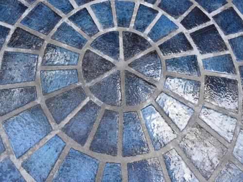 亀崎というまちが、もともと「海」と「井戸」が身近であったことを思い起こさせる「水」をテーマにコバルトの釉薬を調合した。ワイヤーでカットされたタイル表面は水面のさざ波のようだ。上面を施釉することで汚れにくいという機能も付加している。